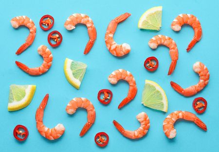 pattern of prawns, lemon and chili on blue background Stock Photo