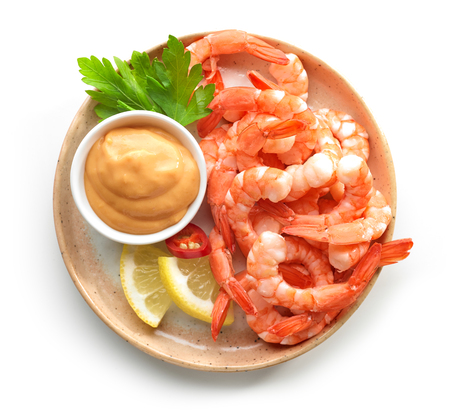 plate of boiled prawns and salsa sauce isolated on white background, top view