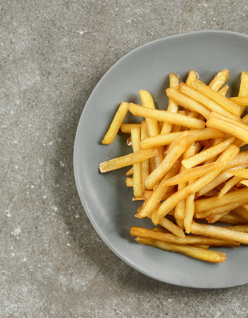plate of french fries on grey kitchen table, top view