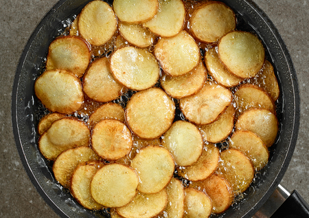 frying potatoes in pan with oil, top view Stock Photo