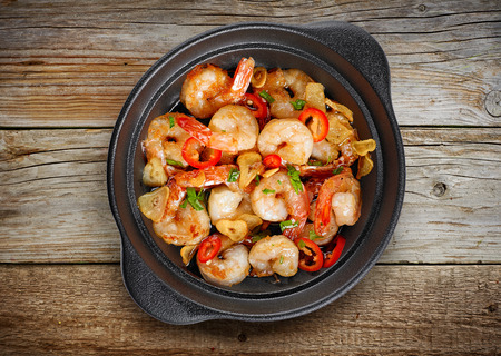 bowl of garlic prawns on wooden table, top view