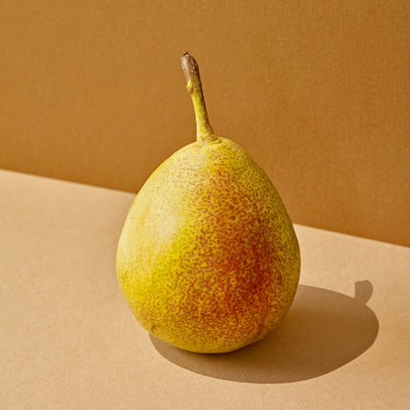 pear with long shadow on colored paper background