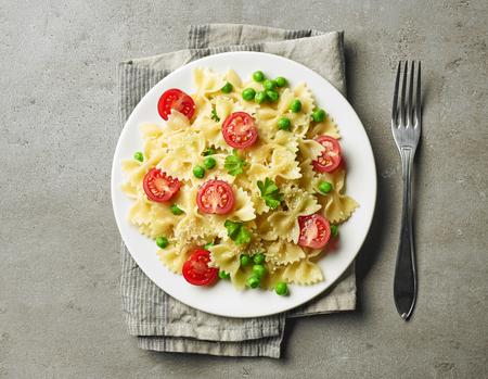 plate of pasta with cheese and vegetables on grey kitchen table, top view