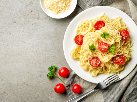 Plate of pasta spaghetti with cheese and tomato, top view Stock Photo