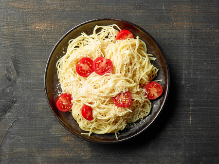 Plate of pasta spaghetti with cheese and tomato on dark wooden table, top view Stock Photo