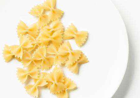 Fresh pasta farfalle on white plate, top view