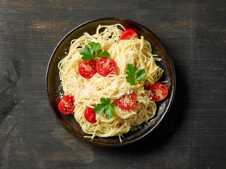 Plate of pasta spaghetti with cheese and tomatoes on dark wooden table, top view