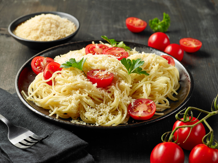 Plate of pasta spaghetti with cheese and tomatoes on dark wooden table Stock fotó