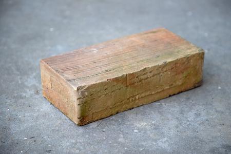 Old brick on grey concrete background Stock fotó