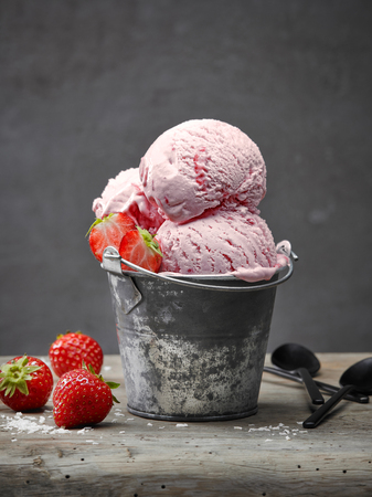 Strawberry and coconut ice cream on wooden table