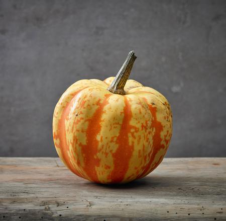 Yellow autumn pumpkin on wooden table Stock fotó