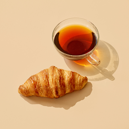 cup of tea and croissant with long shadow on colored paper background