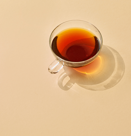 cup of tea with long shadow on colored paper background