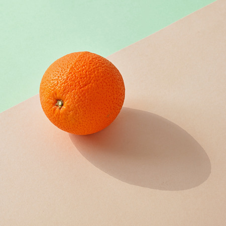 fresh orange with long shadow on colorful paper background