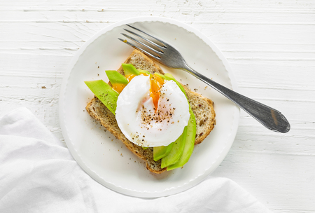 sandwich with avocado and poached egg on white wooden table, top view Stock fotó
