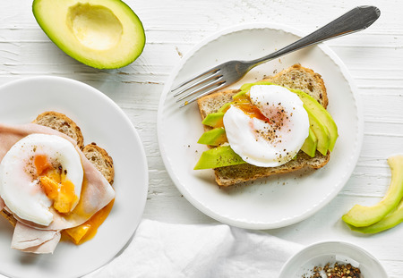 plate of poached egg sandwich and avocado, top view