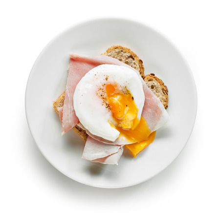 Plate of sandwich with poached egg isolated on white background, top view
