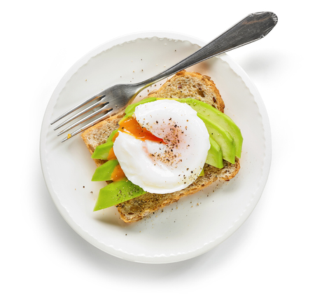 Healthy sandwich with poached egg and avocado on the white plate