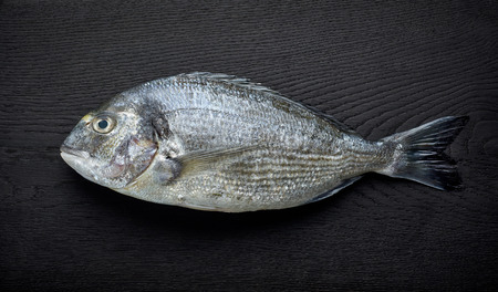 raw sea bream on black wooden board, top view