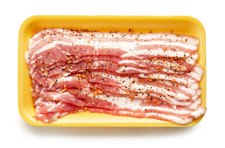 Yellow plastic tray of spicy breakfast bacon isolated on white