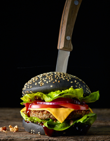 Fesh tasty black burger on wooden board