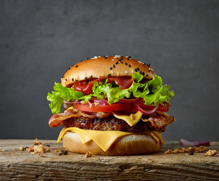 Fresh tasty burger on wooden board