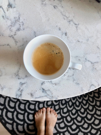 Cup of coffee on marble table, top view