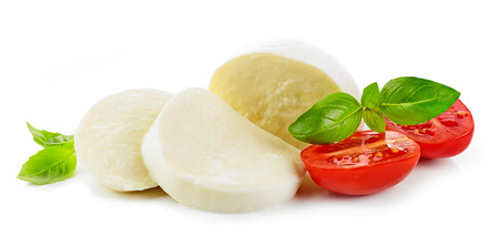 Sliced mozzarella cheese with tomato and basil isolated on white