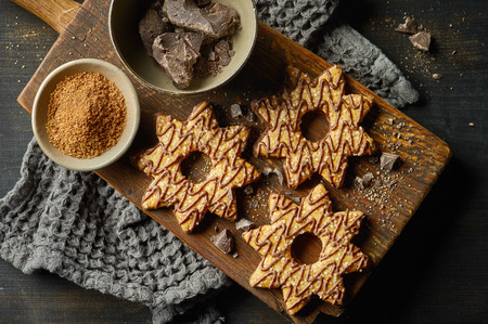 freshly baked cookies decorated with chocolate and sugar on wood board, top view Stock fotó