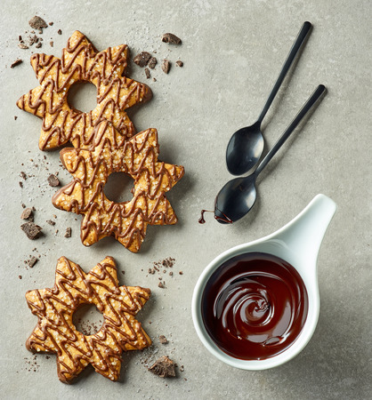chocolate sauce and star shaped cookies on grey background, top view Stock fotó
