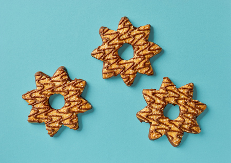 decorative star shaped cookies on blue background, top view