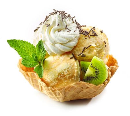 orange ice cream in waffle basket decorated with whipped cream and kiwi isolated on white background Standard-Bild