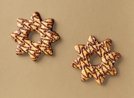 two star shaped cookies on brown background, top view