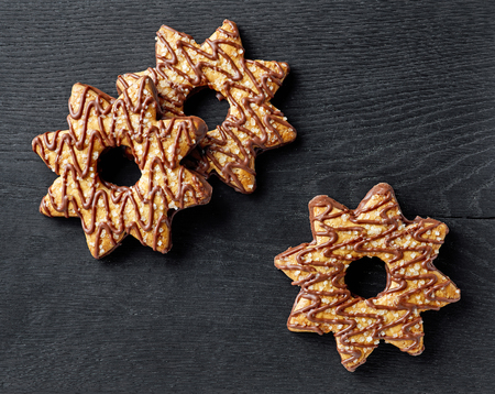 cookies decorated with chocolate on black wooden board, top view