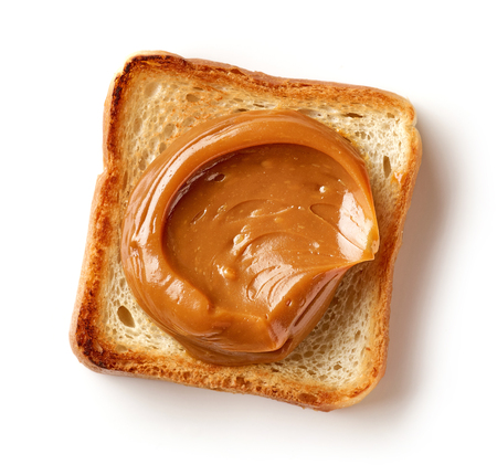 toasted bread slice with melted caramel isolated on white background, top view