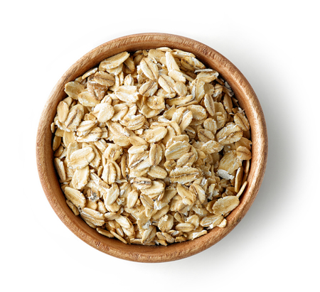 wooden bowl of oat flakes isolated on white background, top view