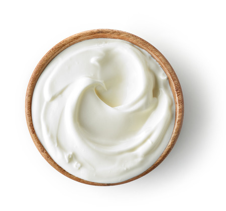 wooden bowl of sour cream or yogurt isolated on white background, top view