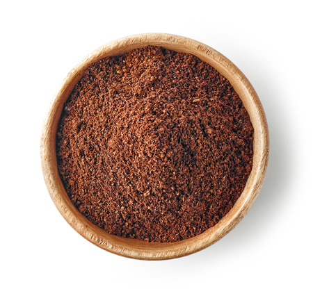 wooden bowl of ground coffee isolated on white background, top view