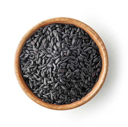 wooden bowl of black rice isolated on white background, top view