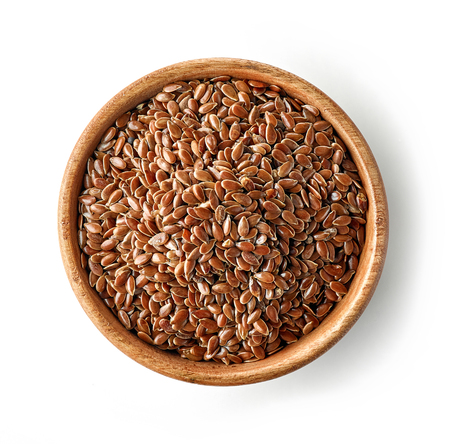 wooden bowl of flaxseed isolated on white background, top view