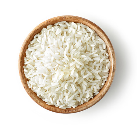 wooden bowl of uncooked rice isolated on white background, top view Stock Photo