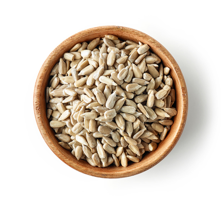 wooden bowl of sunflower seeds isolated on white background, top view