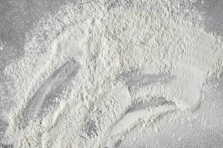 white flour texture on grey kitchen table background, top view