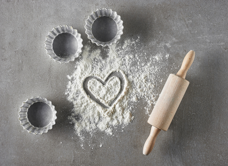 heart shape in flour and baking equipment on grey kitchen table, top view
