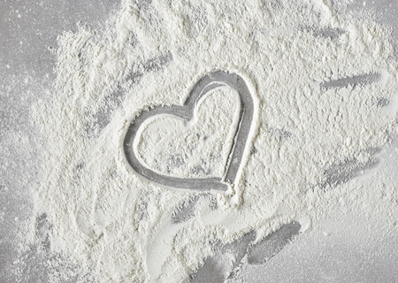 heart shape in flour on grey kitchen table background, top view Stock Photo