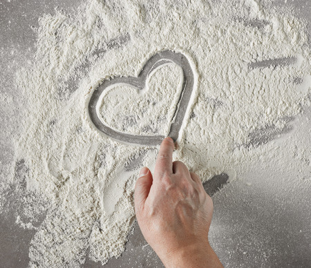 Hand drawing heart shape in flour on grey table, top view Stock Photo