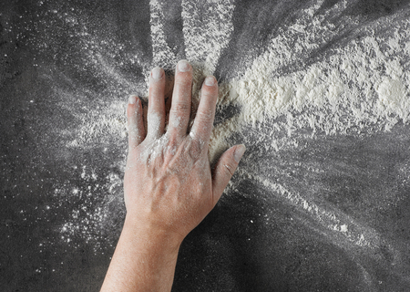 bakers hand with flour in motion on black kitcen table background, top view Stock Photo