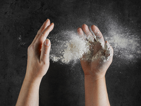 baker hands with flour in motion on grey kitcen table background, top view Stock Photo