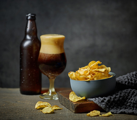 bowl of chips and beer on wooden table
