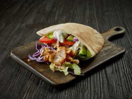 Doner kebab en la mesa de la cocina de madera oscura.